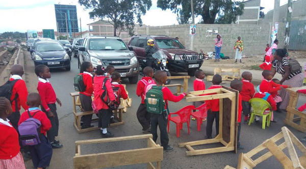 Students placed their desks across the road, blocking morning rush hour traffic.