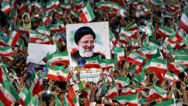 Ebrahim Raisi's supporters loft national flags and his portrait during a campaign rally at Imam Khomeini Mosque in Tehran on Tuesday.