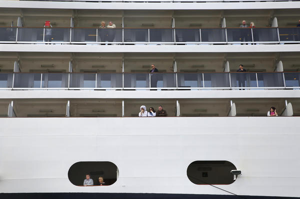 Passengers aboard the Nieuw Amsterdam cruise ship look out at Ketchikan.