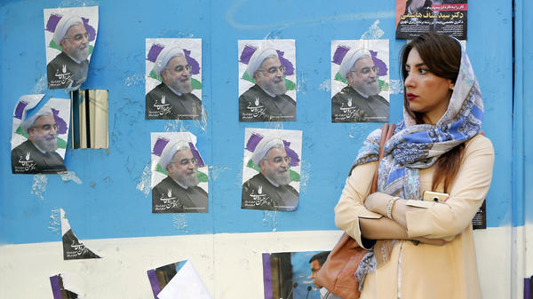 A woman in Tehran stands in front of a wall plastered with posters of Iranian President Hassan Rouhani, whose re-election bid will have its decisive moment Friday — unless, of course, the voting results in a runoff.