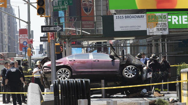 A car rests on a security barrier in New York's Times Square after it plowed through a crowd of pedestrians on Thursday.