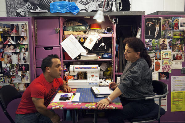 """Performer Paulo dos Santos (left), who plays one of the central characters in """"Out of this World,"""" speaks with Cloty Gutierrez, the head of costume repair."""