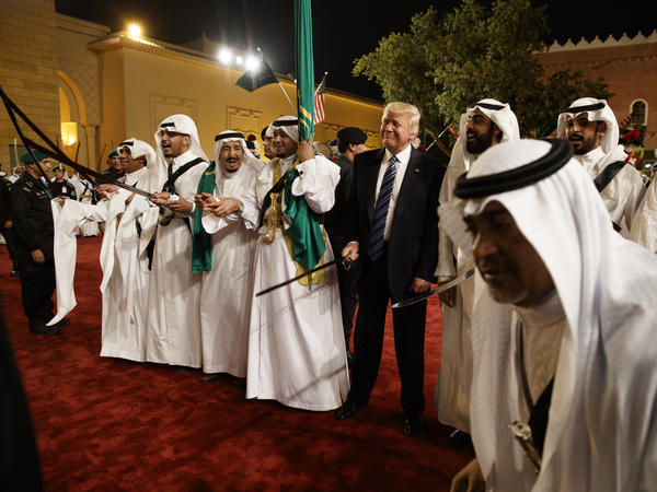 President Trump holds a sword and sways with traditional dancers during a welcome ceremony at Murabba Palace on Saturday in Riyadh.
