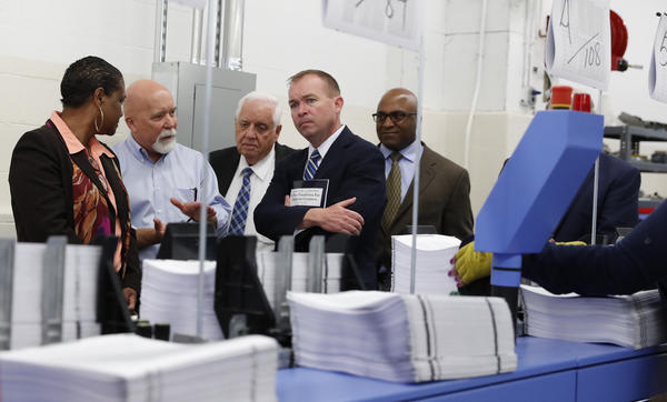 "White House Budget Director Mick Mulvaney (second from right) holds a copy of the president's 2018 budget at the Government Publishing Office's plant in Washington, D.C. Mulvaney describes the plan as ""taxpayer first."""
