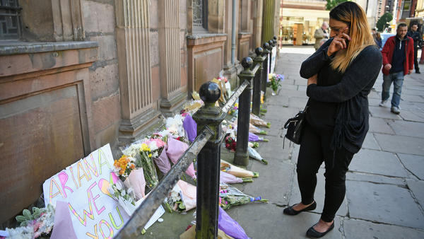 A woman looks at flowers left in Manchester's St. Ann Square on Tuesday, one day after a bomber carried out an attack at the end of an Ariana Grande concert in the city.