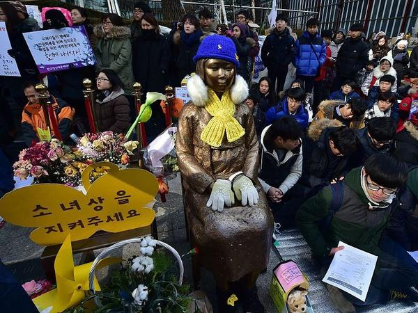 """During a weekly anti-Japanese demonstration, South Korean students sit near a statue of a teenage girl symbolizing former """"comfort women"""" who served as sex slaves for Japanese soldiers during World War II. The statue is seen in front of the Japanese Embassy in Seoul on Feb. 3, 2016."""
