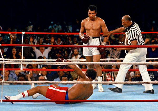 Muhammad Ali (center) watches after knocking down defending heavyweight champion George Foreman.