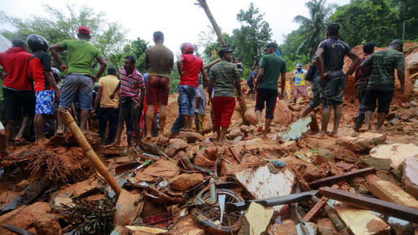 Sri Lankan military rescuers and villagers stand on the debris of a house that was destroyed in a landslide in the village of Bellana, in the Kalutara district of Sri Lanka, on Friday. Mudslides and floods triggered by heavy monsoon rains have killed scores of people in the island nation.