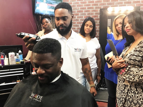 Barber Wade Menendez installs a man weave on client Cliff Holcomb, while his students observe.