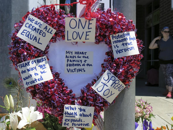 A heart-shaped wreath covered with positive messages hangs on a traffic light pole Saturday at a memorial for two bystanders who were stabbed to death Friday on a light-rail train in Portland, Ore.