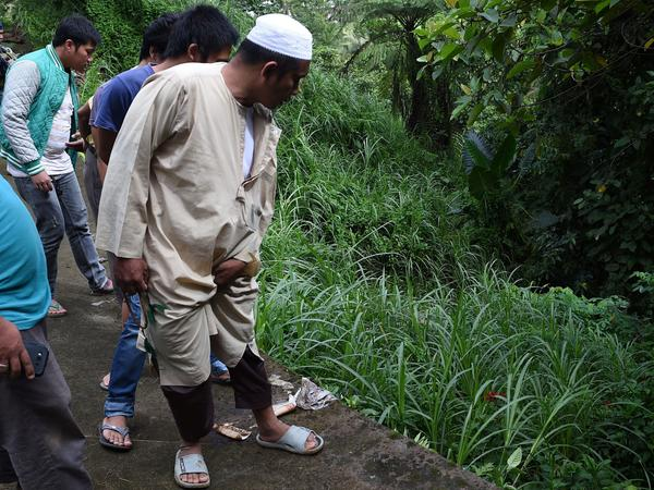 Residents look at bodies found in a ravine on the outskirts of Marawi on the southern Philippine island of Mindanao on Sunday. Nearly 100 people have died as the government tries to drive out ISIS-allied militants.
