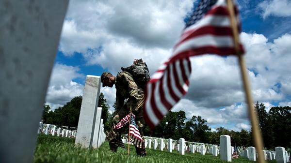 A soldier in the Old Guard places flags at graves in Arlington National Cemetery in preparation for Memorial Day, on May 29.