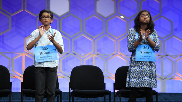 The final two spellers — Rohan Rajeev, 14, (left) from Edmond, Okla., and Ananya Vinay, 12, from Fresno, Calif. — applaud Thursday night during the finals of the 90th Scripps National Spelling Bee, in Oxon Hill, Md.