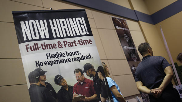 """A """"Now Hiring!"""" sign is displayed next to the Jiffy Lube International booth at a jobs fair in Overland Park, Kan., in March."""