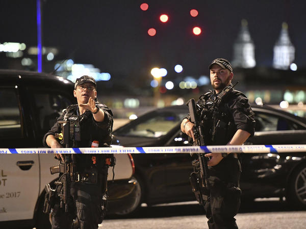 """Armed police officers stand guard on London Bridge in central London. British police said they were dealing with """"incidents"""" on London Bridge and nearby Borough Market in the heart of the British capital Saturday."""