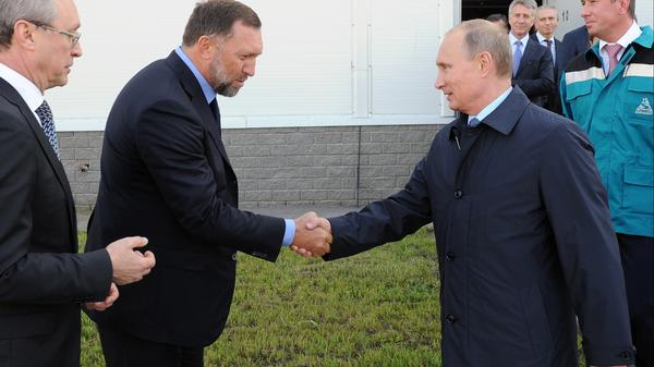 Businessman Oleg Deripaska (left) greets Russian President Vladimir Putin during a visit to a factory in Russia's Nizhny Novgorod region in September 2014.