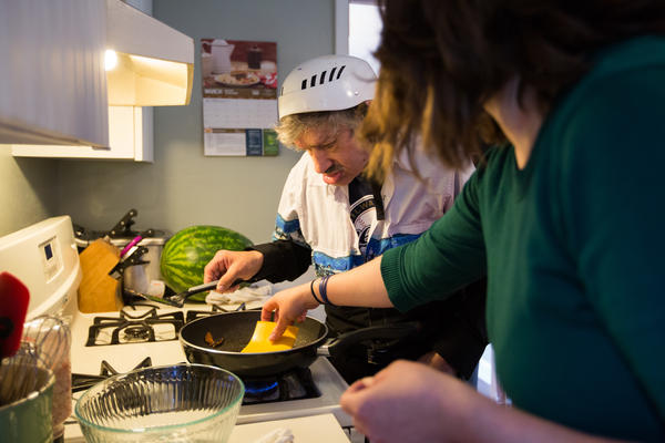 Client John Neu (left) learns to make a cheeseburger with tips from Justine Orr. Our Place Day Services also teaches clients many work skills, how to manage money and how to be more independent socially.