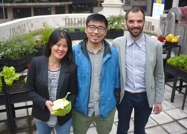 Client Gina Ma (left) stands with Rooftop Republic's Andrew Tsui (center) and Pol Fàbrega amid the rooftop garden of a French restaurant in central Hong Kong.