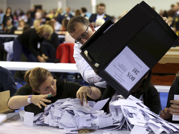 Ballot boxes are emptied to be counted for the general election in Glasgow, Scotland.