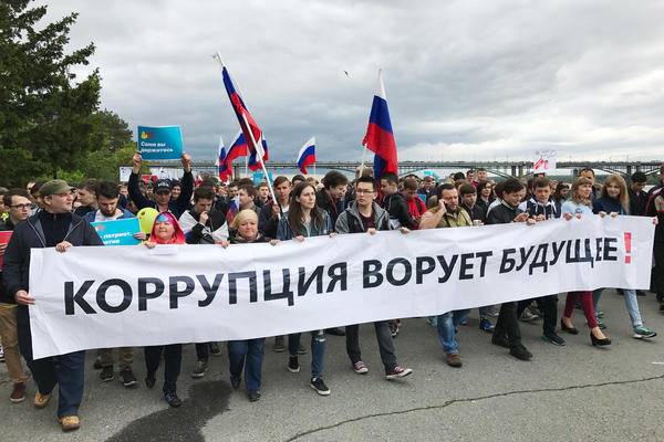 "Anti-government protesters march in Novosibirsk, the capital of Siberia and Russia's third most populous city, with a banner reading ""Corruption steals the future!"""