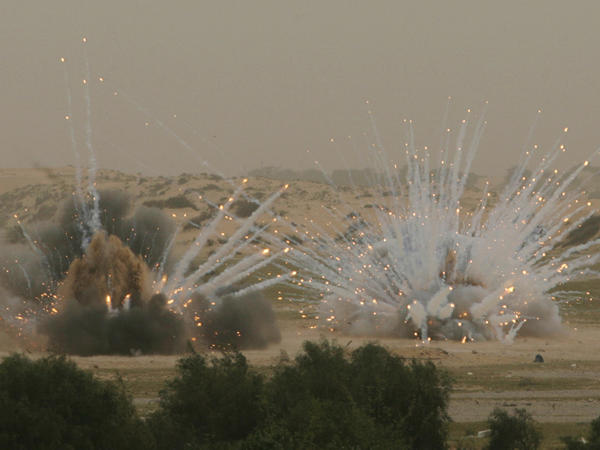 White phosphorus munitions are blown up by U.N. and Hamas sappers, not seen, in the Khan Younis refugee camp in the Gaza Strip in March 2010. The munitions remained unexploded since the Gaza war in 2008, when they were fired.