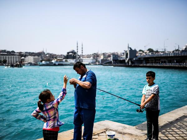 A man and his children go fishing Wednesday in the Karakoy neighborhood of Istanbul.