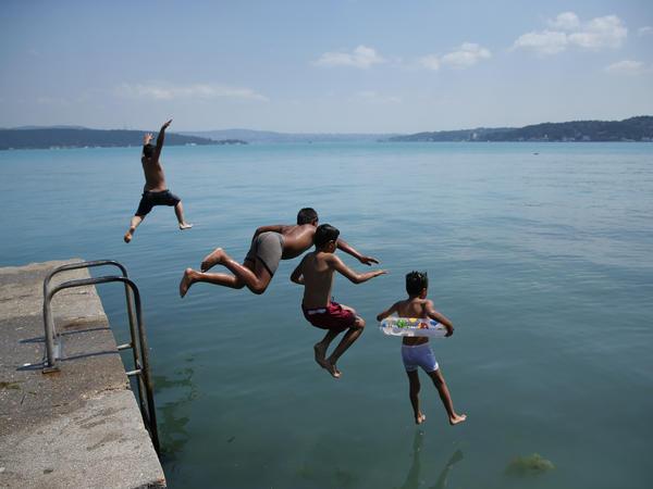 Children jump into Istanbul's Bosphorus Strait on Wednesday.