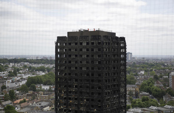 Emergency workers walk on the roof of the fire-gutted Grenfell Tower in London on Friday.