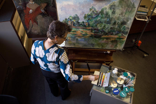 Senior conservator of paintings Ann Hoenigswald works to fill in elements of Paul Cézanne's <em>Riverbank</em> c. 1895 in the National Gallery of Art's Paintings Conservation Lab in Washington, D.C.
