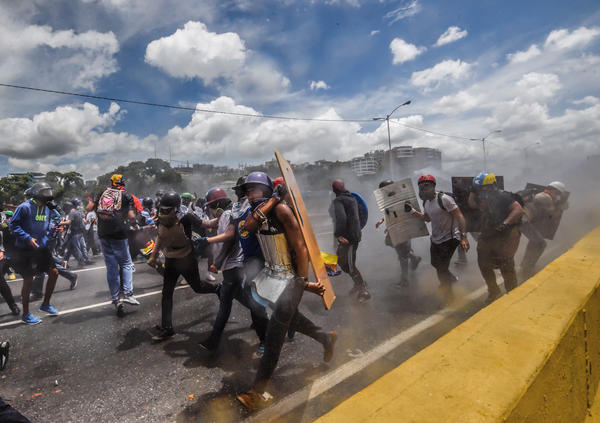 Opposition activists clash with riot police during a demonstration against the government of President Nicolas Maduro along the Francisco Fajardo Highway in Caracas on June 19.