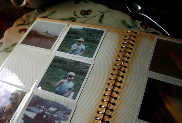 Steve flips through old photographs of their family, pausing on a set of pictures of his son pulling out his own tooth. The back of the photograph reads: the dentist.