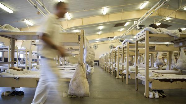 In this June 18, 2015, photo, a prisoner walks near his crowded living area in Elmore Correctional Facility in Elmore, Ala. Tuesday's ruling comes in a class action lawsuit brought by inmates who argued the conditions violated the U.S. Constitution's ban on cruel and unusual punishment.