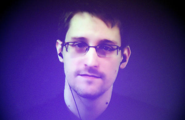 Edward Snowden appears from Russia on a giant video screen in 2014. The former National Security Agency contractor fled to Russia in 2013 shortly after leaking information about the NSA's bulk data collection program. He also faces charges in the U.S. under the Espionage Act.
