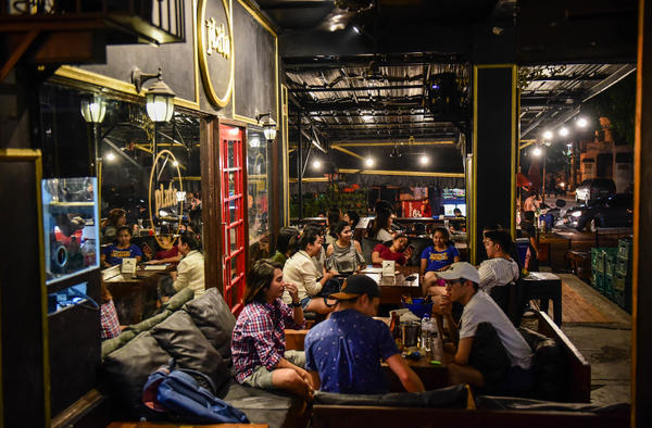 People gather in a bar popular with students from nearby De La Salle University.