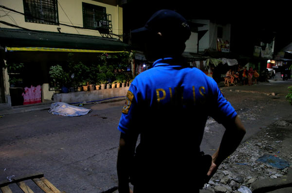 A policeman stands guard near the body of a suspected drug dealer on a street in Quezon City, Metro Manila, on March 1. Police investigators said the victim was shot and killed by unidentified men.