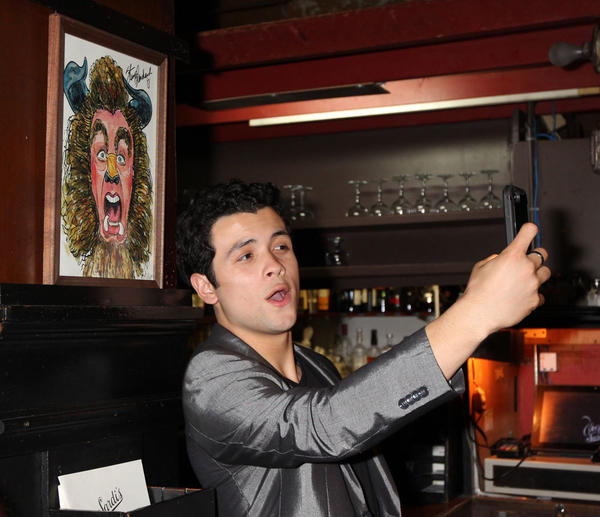 Torrez takes a selfie in front of a caricature of the Beast at Sardi's, a restaurant in the theater district.