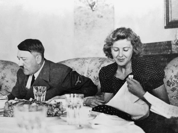 "Berlin, Germany: A candid photograph of Eva Braun with Adolf Hitler at the dining table. A new book explores the lives of six women through food, and Hitler's mistress is a startling inclusion. But what Braun ate reflected a ""perpetual enactment of her own daydream"" against a barbaric backdrop."