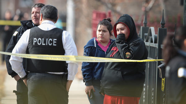 Police investigate the scene of a double homicide in Chicago in February. More than 1,700 people have been shot in the city so far this year.