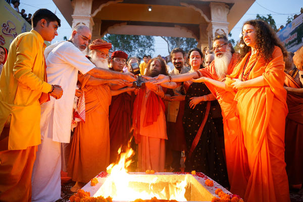 Pujya Swami Chidanand Saraswatiji, center, and Sadhvi Bhagawati Saraswati, far right, join other faith leaders in the <em>yagna, </em>a fire ceremony meant to purify the mind and air, at their ashram beside the flowing Ganges. It precedes the Ganga Aarti, a ritual to show reverence to the river.