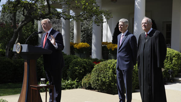 President Donald Trump, accompanied by Supreme Court Justice Anthony Kennedy, right, and Justice Neil Gorsuch speaks in the Rose Garden of the White House on April 10, 2017, before a public swearing-in ceremony for Gorsuch.