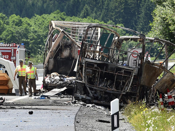 Policemen and forensic experts work at the scene where a tour bus caught fire after hitting a truck on the A9 highway in southeastern Germany.