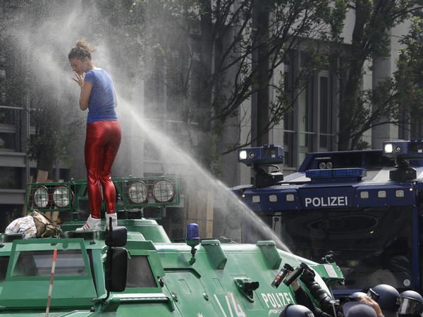 A woman is pepper-sprayed by police after she climbed onto an armored vehicle on the first day of the Group of 20 summit in Hamburg, Germany.