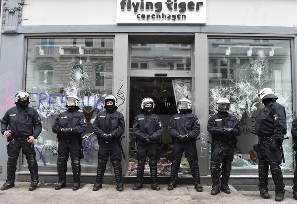 Policemen stand in front of a looted shop after riots struck Hamburg's Schanzenviertel district as the G-20 Summit heads toward its close on Saturday.