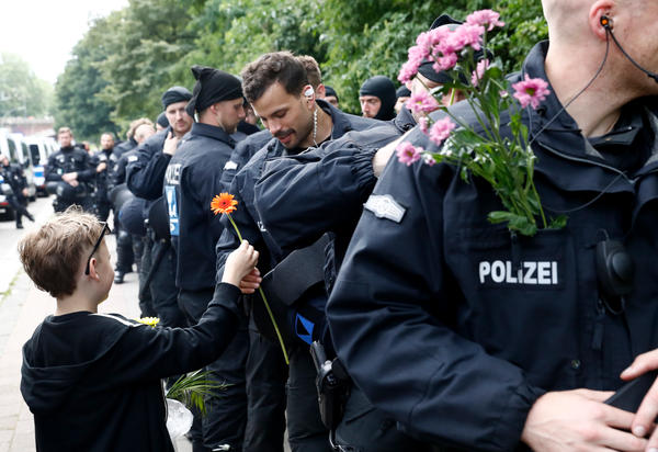 A boy hands flowers to police as they watch a demonstration pass by during G-20 Summit meetings on Saturday.