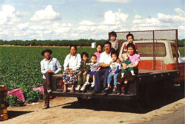 A family photo from the 1990s shows the Yang family sitting on a truck on their farm.