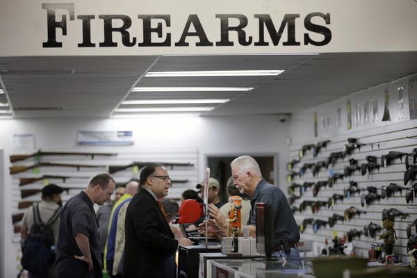 In this Dec. 9, 2015,  photo, sales associate Mike Conway, right, shows Paul Angulo guns at Bullseye Sport gun shop in Riverside, Calif. (Jae C. Hong/AP)