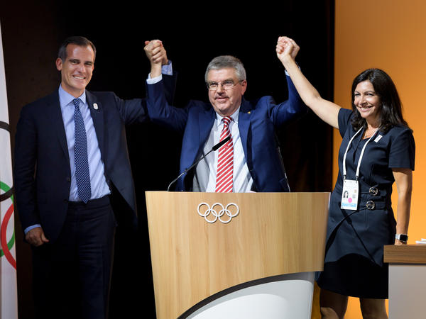 Los Angeles Mayor Eric Garcetti (from left), IOC President Thomas Bach and Paris Mayor Anne Hidalgo raise hands Tuesday in Lausanne, Switzerland, after the IOC voted the cities can work out a deal to host the 2024 and 2028 Olympics.