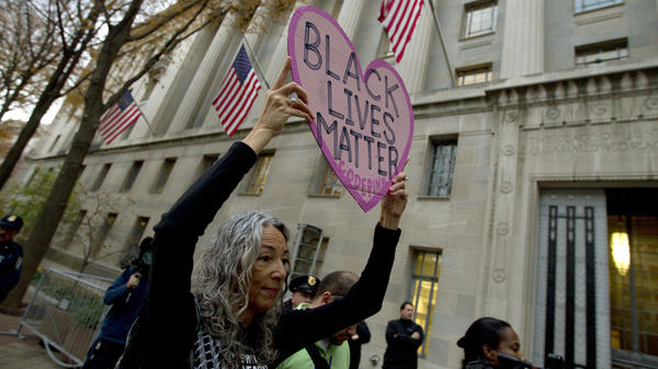 Desiree Fairooz holds up a sign during a protest against the shooting death of 18-year-old Michael Brown at the Department of Justice in Washington, D.C., in 2014. This January, Fairooz was arrested after laughing during the confirmation hearing for Jeff Sessions as attorney general.