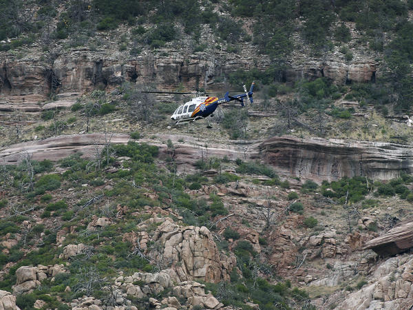 A helicopter flies above the rugged terrain along the banks of the East Verde River during a search and rescue operation for victims of a flash flood on Sunday in Payson, Ariz. Search and rescue crews recovered bodies of five adults and four children.