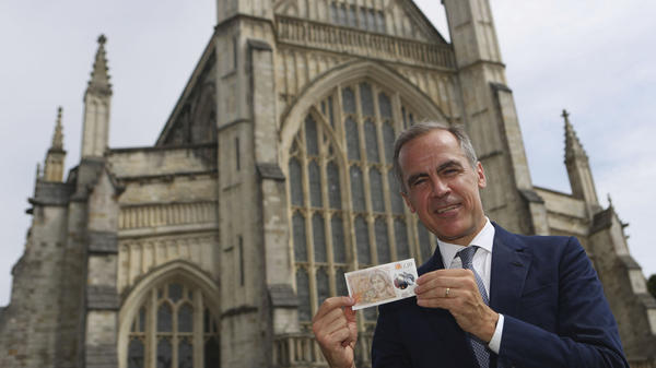 The Governor of the Bank of England, Mark Carney, poses at Winchester Cathedral in England on Tuesday, with the new 10-pound note featuring the image of Jane Austen. Two hundred years to the day since Jane Austen was laid to rest at Winchester's grand cathedral, the bank unveiled a new 10-pound note featuring the beloved author.